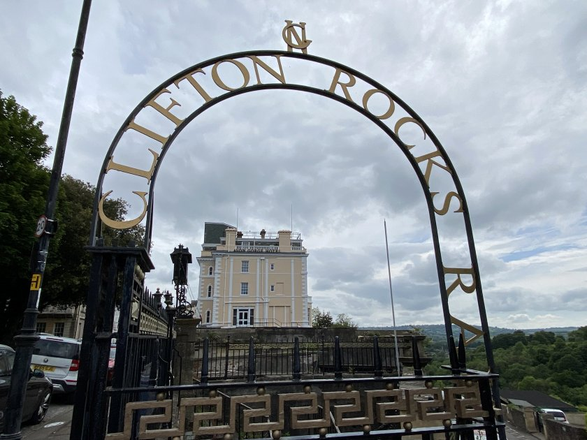 Avon Gorge Hotel framed by a sign for the former funicular, Clifton Rocks Railway